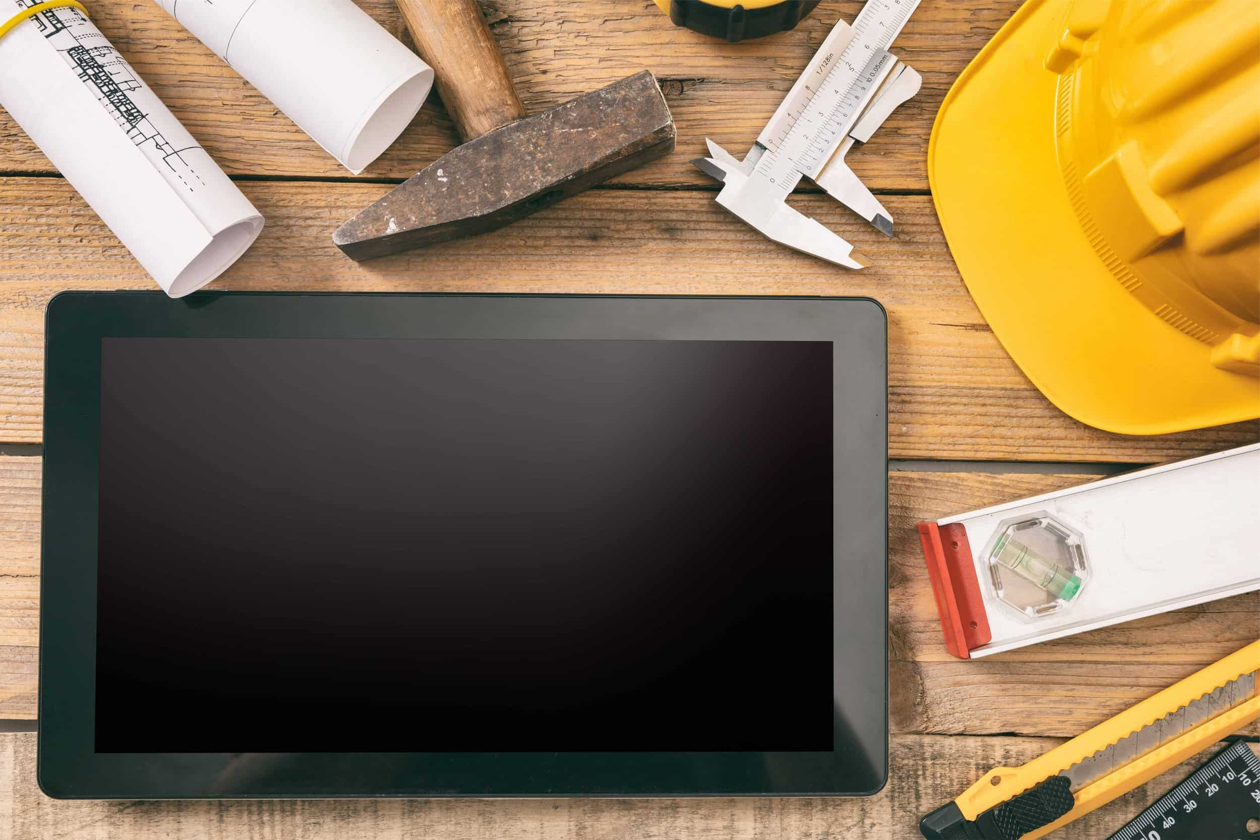 Architect workplace and technology. Tablet with black blank screen, project construction blueprints and engineering tools on wooden desk, copy space, top view